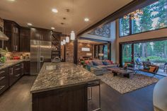 This sophisticated kitchen features modern stainless steal appliances paired with stone countertops and dark shaker style cabinetry. Opening up to the great room, you can walk right in from the sliding glass doors and take a seat at the large kitchen island.
