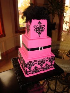 Sweet Sixteen Bday cake - This was a smaller version of a weddng cake I did....And it was HOT pink, to match the venue....it was s 4,6 and 8 inch square...just a little guy...and it was coveredin MMF and black RI for the damasking, I bought the jewelled buckle from MIcheals, and the feathers on top..Thanks for looking Nicole