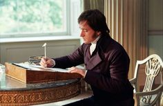 Mr Darcy writes a letter to his sister on a small portable desk. Still from Pride and Prejudice (2005) starring Matthew Macfadyen and Keira Knightley.