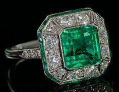 Art Deco ring put with emerald and diamonds in platinum. Especially the typesetting of the rim calibrated cut emeralds betrayal of the high quality of work in this ring.