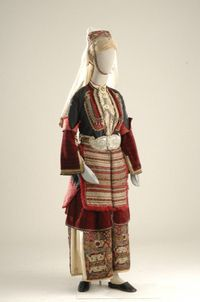 This bridal costume was worn in the 10 villages on the plain northeast of Naousa. In a simplified version without bridal ornaments, it was the everyday dress of the women of Episkopi, and an even simpler version was worn by the elderly (widows). It consists of a long white chemise, the kamouhas, with embroidered decoration, the sayias worn over the chemise, and the fouta, an apron with interwoven decoration, at the waist. The bridal costume has an unusual headdress, the poulisia skepi, with…