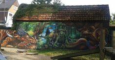 Wandmalerei von Grafittikünstlern an einer Hauswand in Burg. Es zeigt die Mythen und Sagen des Spreewaldes.