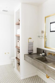 Gold and gray bathroom features a brass mirror, Bistro Polished Brass Mirror, lit by Schoolhouse Electric Orbit Sconces placed over a floating concrete washstand and sink fitted with a Kohler Purist Faucet.