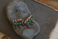 A simple, lightweight triangular framed assemblage of copper, batik patterned pipe bone, genuine Turquoise nuggets and Czech glass...a summer mood earring that is versatile in its earthy palette with the always versatile Turquoise accent. Mottled Czech daggers in soil, mustard and lichen hang spaced below via secured waxed cord. All copper has been oxidized and later coated in a layer of Renaissance wax for preservation. Ear wires are minimally formed using 20 gauge HH copper. Length from…