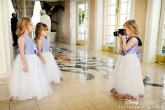 A flower girl plays photographer to her two younger sisters at Disney's Grand Floridian Resort & Spa.