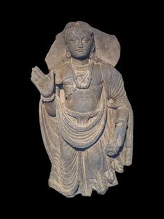 Bodhisattva en schiste.  Il est représenté debout exécutant de la main droite le geste d'absence de crainte. Il est vêtu du paridhana et de l'uttariya qui laisse le torse dénudé et porte la parure des Bodhisattvas. Les cheveux noués sur le sommet du crâne par un nœud transversal « krobylos ».  H : 45 cm.  Art gréco-bouddhique du Gandhara (Ier-Ve s.)