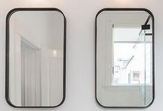curved edge mirrors above sinks