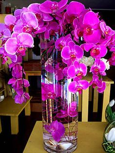 Purple Orchids floating in cylinder with pink wires and flowing out of the top. I would like it better if the orchids on top sat up higher out of the vase and there were other flowers with the orchids on top for more interest.