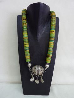 Necklace   Kim Price.  Green, yellow and red shades of vulcanite heishi combined with a Moroccan pendant