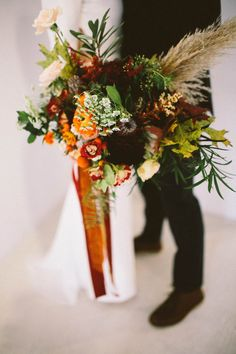 Moody orange, red, and green bridal bouquet | Image by Alyssa McElheny Photography