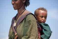 Women in Ethiopia walk an average of four hours each to collect drinking water — many with a child on their backs.