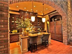 Tuscan kitchen with pendant lights and stone arch.  The Tuscan style lighting is great in this Tuscan kitchen.