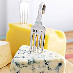CHEESE MARKERS: Say cheese! To make these cheese markers, place vintage silver-plated forks between felt pieces and flatten in a vise. Place the front side up on a metal block and use metal stamps and a hammer to mark the name of the cheese. Cut off the top few inches of the handle, then make a curly loop by wrapping the handle in felt and curling it backward using pliers.