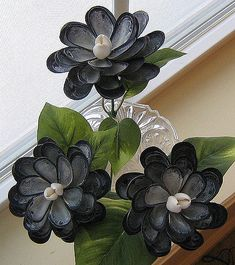 Three seashell flowers made with naturally blue mussel seashells.