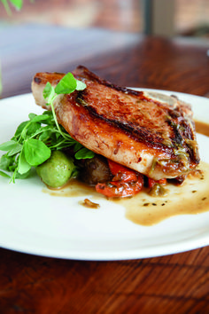 Grilled pork chop served with seared radicchio, spring garlic, and fava bean shoots. The menu at Wyebrook Farm changes daily based on available seasonal ingredients (By: Sue Long; photo by: Matthew Tennison. July 2015) #pork #favabeans #radicchio #garlic #wyebrook #farm #lancastercounty