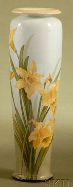 A Doulton Lambeth Faience glaze Pottery Vase, ivory body and of tall slender tapered form decorated with daffodils and green leafy stems on a pale blue ground, England, circa 1890-1900