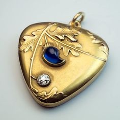 Art Nouveau locket pendant by Moscow jeweller Feodor Lourie, between 1899 and 1908.   Antique 14k gold, embellished with oak leaves, a carved blue sapphire suggesting an acorn, and an old European-cut diamond. Locket contains two miniature picture frames.