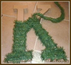 Cut out cardboard letter. Wrap it in garland. Add a red bow or an ornament or two....voila...cheap wreath.