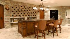 """This finished basement has a wine rack built into the stone walls and a granite wet bar. The liquor safe has a cheeky """"Fort Knox"""" sign on the door. What do you think of this basement? Rustic Basement Bar, Small Basement Bars, Basement Bar Plans, Man Cave Basement, Basement Ideas, Basement Storage, Basement Flooring, Man Cave Designs, Wine Cellar Design"""