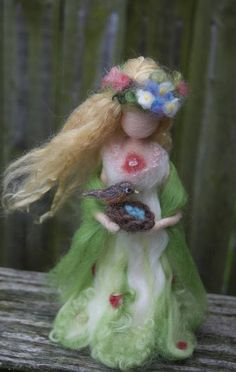 This was a special commission for a Spring Goddess, the first in a set of four Seasons goddesses. I can create a similar or customized one for you. She is clothed in wool dyed with eco-friendly dye with a spring green and floral theme. She holds a robins nest with the robin and