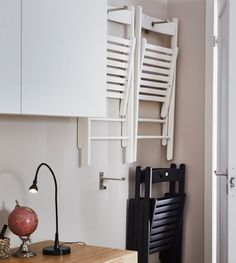 Extra fold-up chairs are hung on a wal behind the living room door.