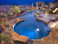 Evening ambiance was the design goal for this pool and spa by Alderete Pools. Pentair LED multicolored lights enhance the nighttime feel and the attached patio features a full stone fireplace. Photography by Andy Abrecht