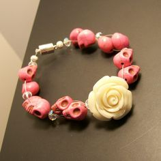 This beautiful sugar skull bracelet is hightlighted by a pretty Ivory rose and pretty pink Sugar Skulls. The skulls are separated by clear faceted glass beads. The inch bracelet is finished with a magnet clasp, fitting the bracelet snuggly to your wrist. Faceted Glass, Glass Beads, Sugar Skull Jewelry, Pink Sugar, Skull Bracelet, Halloween Jewelry, Classy And Fabulous, Day Of The Dead, Pretty In Pink