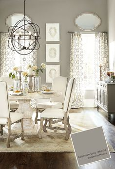 Gray dining room with pedestal table and white upholstered chairs