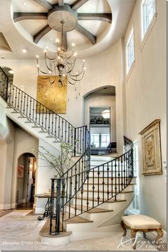 The two story entrance is dominated by the winding staircase.  Decorator for this room is Trisha Dodson.  The stairs lead to a study that is between the first and second floors. The chandelier is the homeowners.