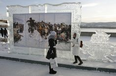 """Two girls look at reproductions of work by Russian classical painter Vasily Surikov, displayed in ice frames, during the 1st International festival of snow and ice sculpture called """"The Magical Ice of Siberia"""" on a bank of the Yenisei in Krasnoyarsk, Russia on January 14, 2013. (Ilya Naymushin)"""