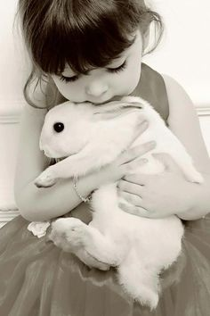 A little girl holding her white rabbit in her arms.