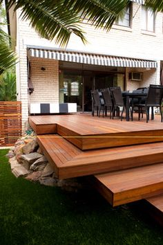 L shaped wood decking seating and armchairs with cushions for Design couchtisch multilevel l