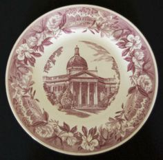 The 1954-1955 commemorative Wedgwood plate.  The Administration Building in the center is bordered by a repeating image of Lake Byron and the bridge, pine cones, camellias, azaleas, and magnolias.