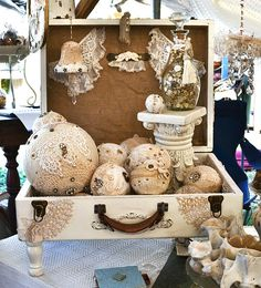 Spheres covered in lace display in suitcases I could so do this suitcase in a linen cloth or cream old white paint