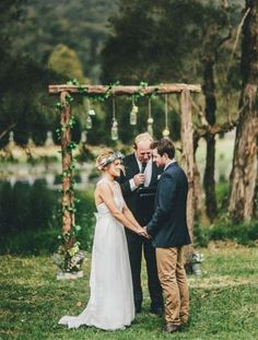 rustic wood wedding arch with greenery and jars