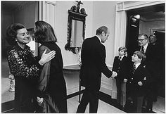 First Lady Betty Ford and Happy Rockefeller Embracing as President Gerald Ford Greets Vice President Nelson A. Rockefeller and the Couple's Two Sons.  ~ December 19, 1974