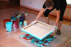 Cassandra Tondro pressing canvas into paint for abstract art