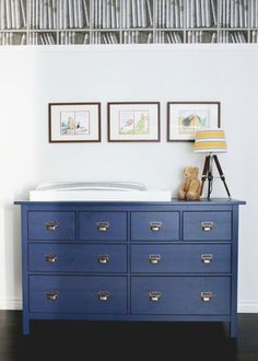 This contemporary, library-themed nursery has a neutral color palette of pale blues and white walls contrasting with a pop of purple for a mature design. Repainting your vintage dresser in BEHR paint in Deep Azure will instantly brighten up your kids' room.