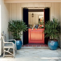 Bold Hue: Lively coral Dutch doors flanked by black-green panels provide bold contrast for a strong style statement. Matching potted plants soften this entryway and lend additional color.