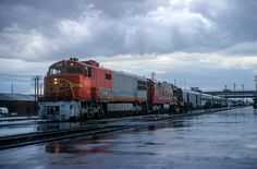 https://flic.kr/p/TDMDVv | Train in the Rain | Santa Fe Train No. 24, Albuquerque, New Mexico, August 26, 1968, engines 402 and 357. Photo by Joe McMillan.