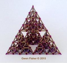 This large beaded bead is a study in the symmetry of a tetrahedron, which is a pyramid with a triangular base. It is composed of 4 large sized tetrahedrons, each of which is composed of 4 medium tetrahedrons, each of which is composed of 4 tiny tetrahedrons, for a total of 64 tiny tetrahedrons. This particular arrangement is known as a third generation Sierpinski tetrahedron, named after Waclaw Sierpinski. Waclaw Sierpinski was a 20th century Polish mathematician who pioneered the field of…