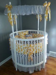 Modern White Round Baby Crib with Amazing Gray Themed Canopy Accessories also White Circle Pattern Yellow Pillows on the Mattress for Baby Nursery Furniture Design Ideas