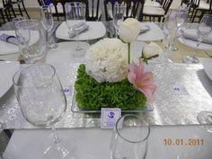 colocado sobre una base de cristal, este diseño con una cama de puras campanitas irlandesas y sobre este hermoso follaje se coloco un topiari de claveles blancos, así como unas rosas tipo polo que sobresalen de el y un toque de lilies en tonalidad rosada para darle un detalle único.