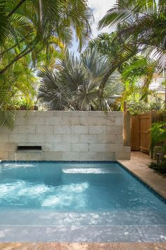 A rustic stone wall features a sleek waterfall that pours into the contemporary swimming pool at this historic Key West cottage. Palm trees and…