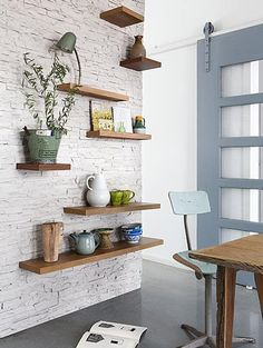 love the random wood shelves on the exposed brick wall.