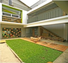 Central courtyard, boardwalk, grass, sand. Shining Stars Kindergarten Bintaro / Djuhara + Djuhara