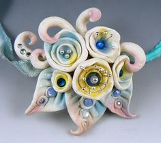 "By Christi Friesen: This ""Snowflower"" was created as an article for ""Bead"" magazine (UK), with the intent that this was a flower that would poke up out of the snow, like edelweiss... so soft and fluffy and gently-colored.  I like the end result of this fantasy flower.  It's accented with sterling ball-tipped pins and Swarovski crystals. Handmade polymer clay art by Christi Friesen"