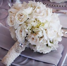 All white roses, white spray roses, white hydrangeas, with the addition of blush spray roses. Dangling pearl loops to be added around outside of bouquet. Handle to be covered in beaded lace (small touch of stems showing, so flowers can get water) Mom to provide brooch for handle. Bouquet by Karen Tran