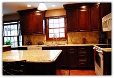We took this kitchen from drab to fab using Greenfield's Custom Cabinets in a rich Cherry finish, New Venetian Gold Granite Countertops, a Tumbled Stone Backsplash with Burgandy Glass Accent Tiles and Laminate Flooring.