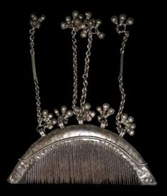 Ebony & Silver Comb | Rajasthan, Northern India | early 20th century or earlier | This fine ebony wood half-moon comb is encased in ornamented silver with dangling chains and jingles. According to Cruse (2007, p. 108) it is, by repute,  from the Jaiselmer region, in Rajasthan, high up on the Pakistani frontier with India. | The Jen Cruse Collection